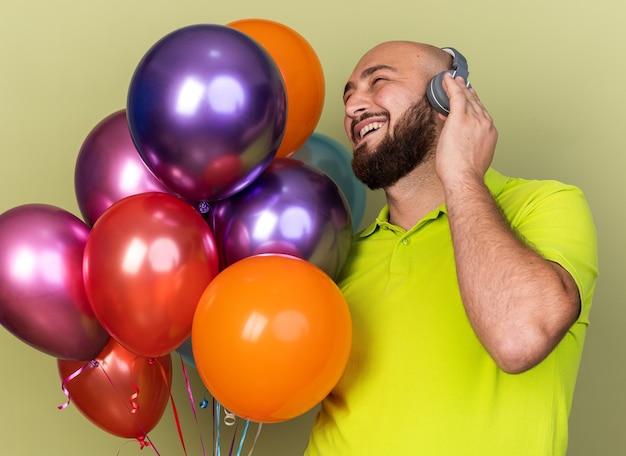 Uśmiechnięty patrzący bok młody człowiek ubrany w żółtą koszulkę i słuchawki, trzymający balony izolowane na oliwkowozielonej ścianie