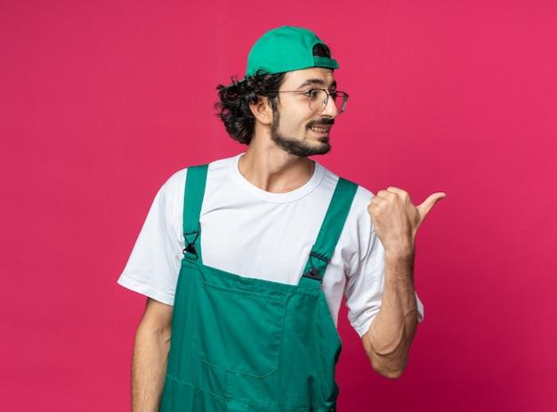 Uśmiechnięty patrzący z boku młody budowniczy mężczyzna ubrany w mundur z czapką wskazuje z boku