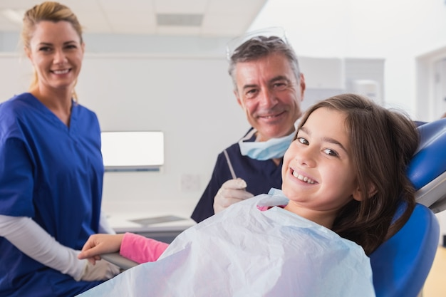 Uśmiechnięty pediatryczny dentysta i pielęgniarka z młodym pacjentem