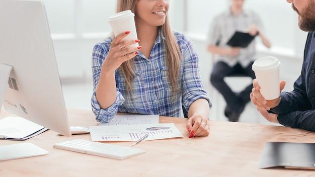 Uśmiechnięty personel omawiający dokument biznesowy podczas przerwy na kawę