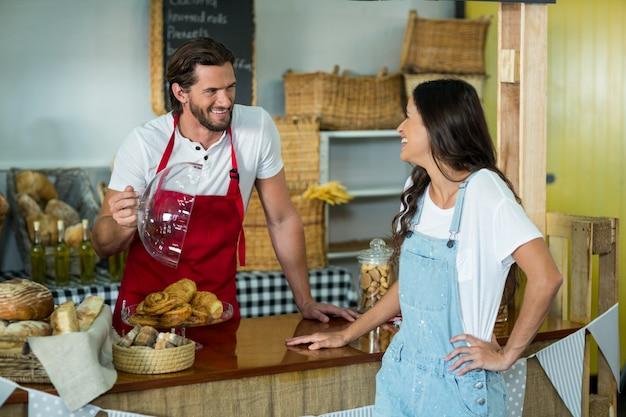 Uśmiechnięty personel piekarni pokazuje przekąskę klientowi płci żeńskiej przy kasie