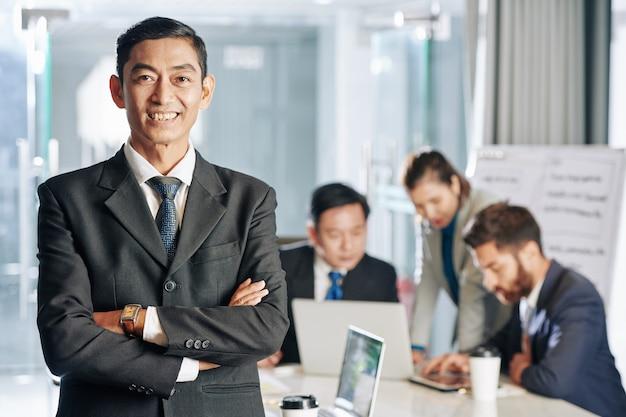 Uśmiechnięty pewny azjatycki przedsiębiorca