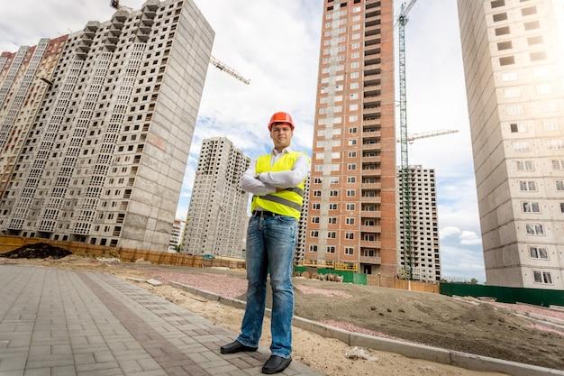 Uśmiechnięty pewny siebie architekt stojący przy budowanych budynkach