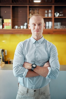 Uśmiechnięty pewny siebie kierownik kawiarni