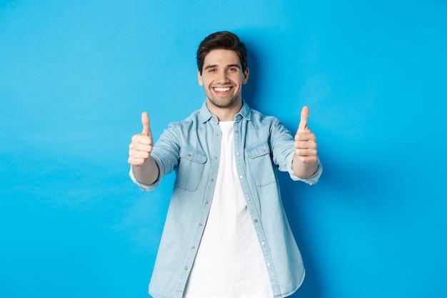 Uśmiechnięty pewny siebie mężczyzna pokazujący kciuki do góry, gwarantujący jakość, aprobujący coś dobrego, stojący na niebieskim tle.