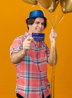 Uśmiechnięty pewny siebie przystojny kaukaski mężczyzna w niebieskim kapeluszu imprezowym trzyma balony z helem i kartę kredytową