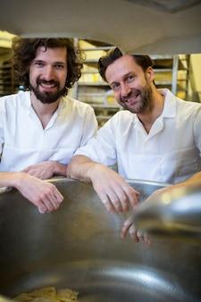 Uśmiechnięty piekarze stojących przy maszynie ciasta