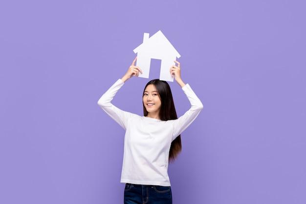 Uśmiechnięty piękny azjatycki kobiety mienia domu symbolu koszt stały odizolowywający na purpury ścianie