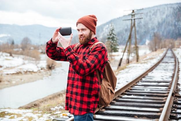 Uśmiechnięty piękny młody człowiek w kraciastej koszuli i kapeluszu robiący zdjęcia w górach