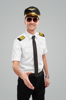 Uśmiechnięty pilot linii lotniczych wyciągający rękę po uścisk dłoni