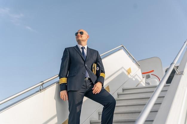Uśmiechnięty pilot odwracający wzrok na drabinie samolotu