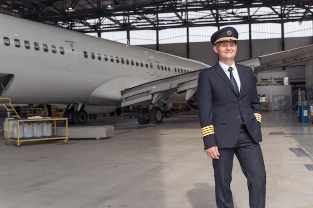Uśmiechnięty pilot pozujący na tle samolotu w hangarze