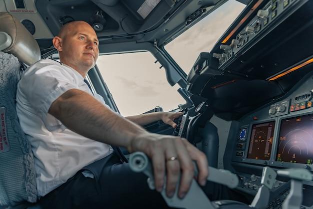 Uśmiechnięty pilot siedzący w lecącej kabinie samolotu