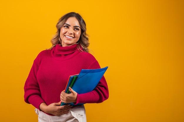 Uśmiechnięty plus rozmiar kobieta studentka z podręczników szkolnych w ręce na żółtym tle.