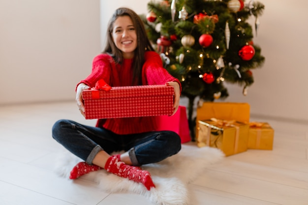 Uśmiechnięty podekscytowany ładna kobieta w czerwonym swetrze siedzi w domu na choinkę, rozpakowywanie prezentów i pudełka na prezenty