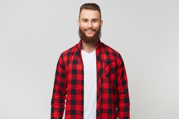 Uśmiechnięty podekscytowany zabawny młody atrakcyjny brodaty mężczyzna, ubrany w koszulę w kratkę, ma szczęśliwy radosny pozytywny wyraz twarzy, uśmiechnięty, na białym tle