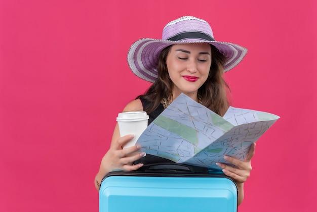 Uśmiechnięty podróżnik młoda dziewczyna ubrana w czarny podkoszulek w kapeluszu trzymając mapę i filiżankę kawy na czerwonym tle