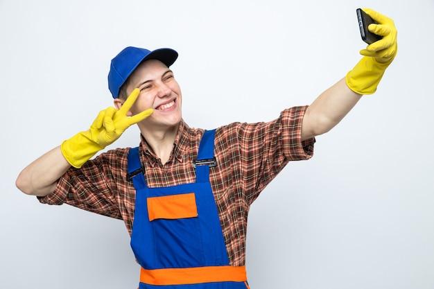 Uśmiechnięty pokazując gest pokoju młody sprzątacz ubrany w mundur i czapkę z rękawiczkami robi selfie