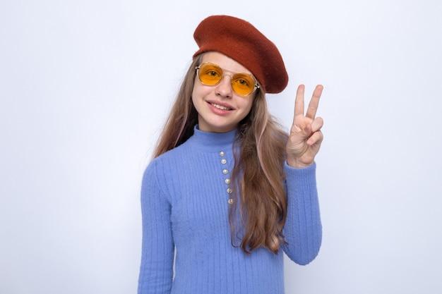 Uśmiechnięty pokazując gest pokoju piękna mała dziewczynka w okularach z kapeluszem na białym tle na białej ścianie