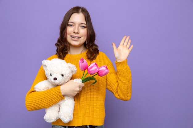 Uśmiechnięty pokazując gest powitania piękna młoda dziewczyna w szczęśliwy dzień kobiety trzymająca kwiaty z misiem na białym tle na niebieskiej ścianie