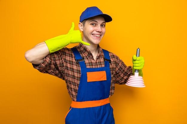 Uśmiechnięty pokazując gest rozmowy telefonicznej młody sprzątacz ubrany w mundur i czapkę z rękawiczkami, trzymający tłok