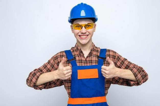 Uśmiechnięty pokazując kciuk do góry młody mężczyzna budowniczy ubrany w mundur i okulary
