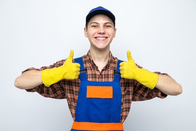 Uśmiechnięty pokazując kciuk do góry młody sprzątacz ubrany w mundur i czapkę z rękawiczkami