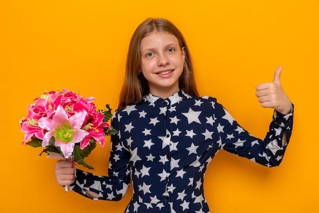 Uśmiechnięty pokazując kciuk do góry piękna mała dziewczynka trzyma bukiet