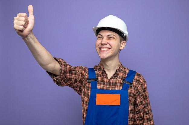 Uśmiechnięty pokazując kciuk w górę młodego męskiego budowniczego noszącego mundur