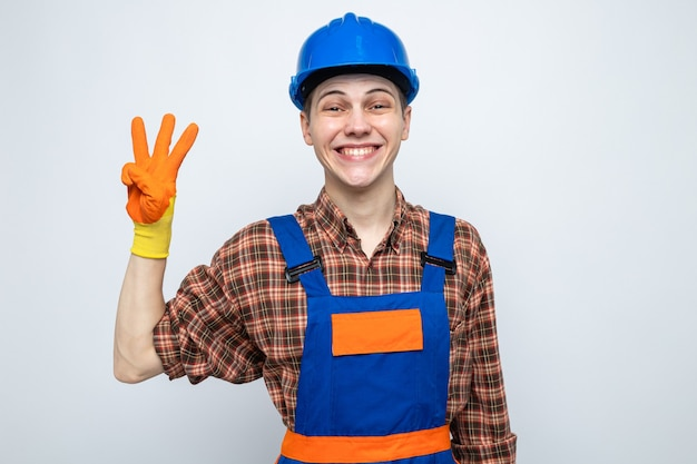 Uśmiechnięty pokazując trzech młodych budowniczych mężczyzn ubranych w mundur z rękawiczkami