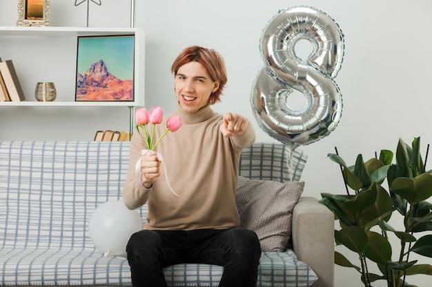 Uśmiechnięty pokazujący gest przystojnego faceta w szczęśliwy dzień kobiety trzymający kwiaty siedzący na kanapie w salonie