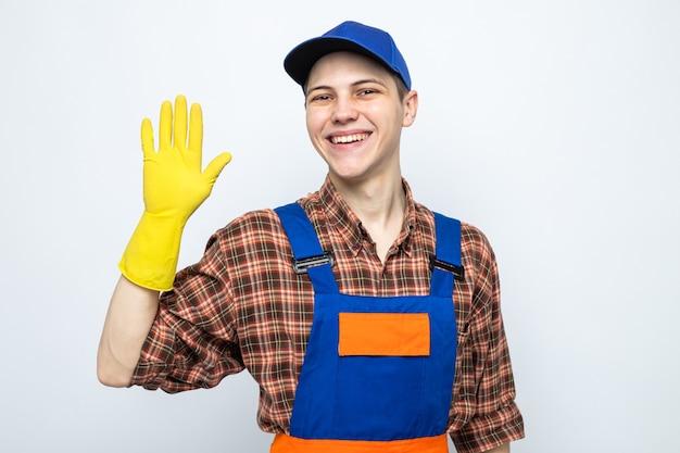 Uśmiechnięty pokazujący powitalny gest młody sprzątacz ubrany w mundur i czapkę z rękawiczkami