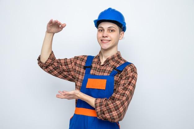 Uśmiechnięty pokazujący rozmiar młody mężczyzna budowniczy ubrany w mundur