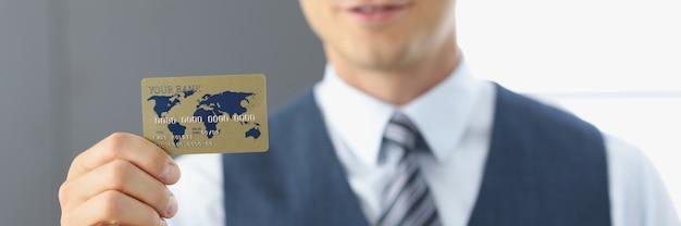 Uśmiechnięty portret biznesmena trzymającego w ręku plastikową kartę bankową