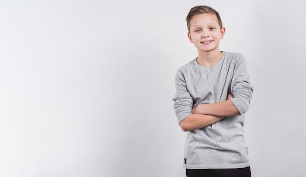 Uśmiechnięty portret chłopiec z jego rękami krzyżował patrzeć kamera przeciw białemu tłu