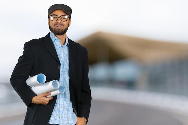 Uśmiechnięty portret czarny architekta inżyniera projektant z planami budowy