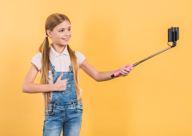 Uśmiechnięty portret dziewczyna pokazuje kciuk up podpisuje brać selfie z mobilnym kijem przeciw żółtemu tłu