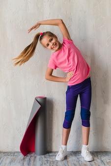 Uśmiechnięty portret dziewczyny robi ćwiczenia rozciągające przed betonową ścianą