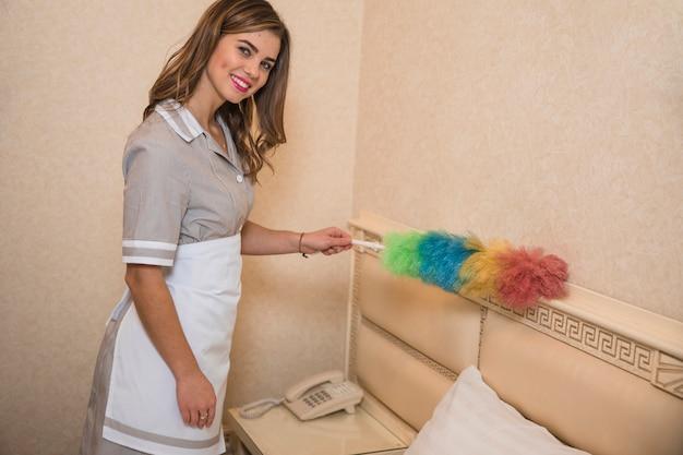 Uśmiechnięty portret gosposia czyści pył z miękkim piórkiem