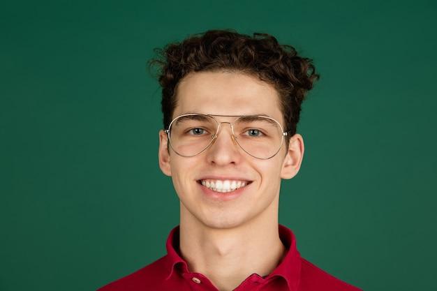 Uśmiechnięty. portret kaukaski przystojny mężczyzna na białym tle na zielonym tle z copyspace.