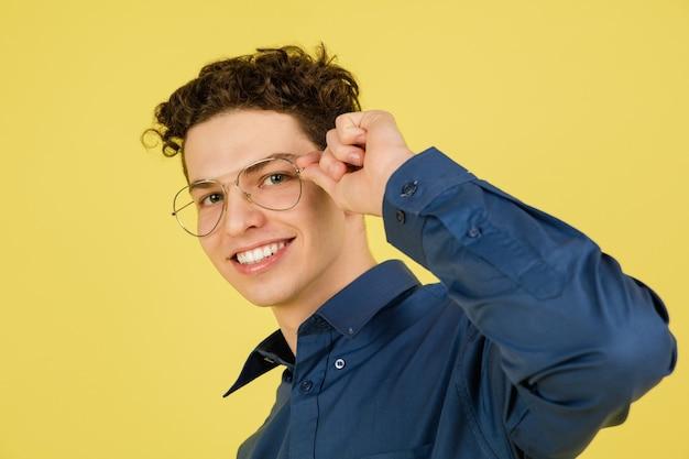 Uśmiechnięty. portret kaukaski przystojny mężczyzna na białym tle na żółtym tle z copyspace.