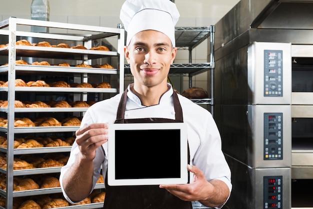 Uśmiechnięty portret męski piekarz w mundurze trzyma małą pustą cyfrową pastylkę przy piekarnią