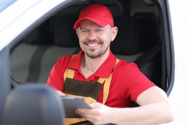 Uśmiechnięty portret męskiego kierowcy kuriera trzymającego dokumenty w oknie samochodu
