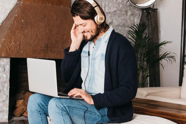 Uśmiechnięty portret mężczyzna używa cyfrową pastylkę dla słuchać muzykę na hełmofonie