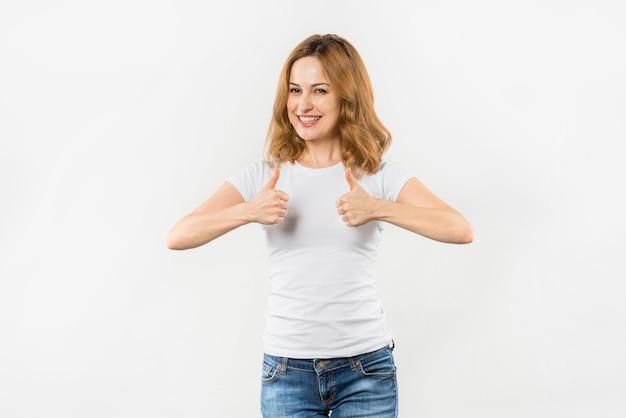 Uśmiechnięty portret młoda kobieta pokazuje kciuk up podpisuje przeciw białemu tłu