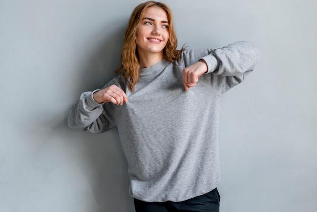 Uśmiechnięty portret młoda kobieta szczypa jej koszulkę patrzeje daleko od przeciw popielatemu tłu