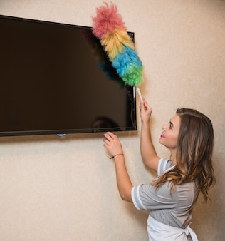 Uśmiechnięty portret młoda kobieta używa duster czyścić ekran telewizyjnego na ścianie