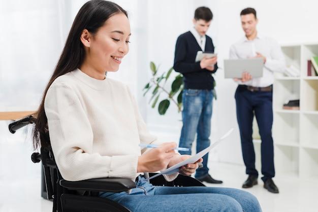 Uśmiechnięty portret młoda niepełnosprawna kobieta czyta dokument przed dwa biznesmenów pozycją w tle