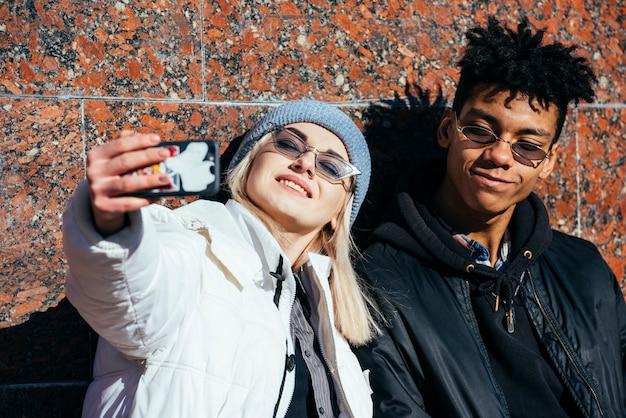 Uśmiechnięty portret młoda para bierze selfie na telefonie komórkowym