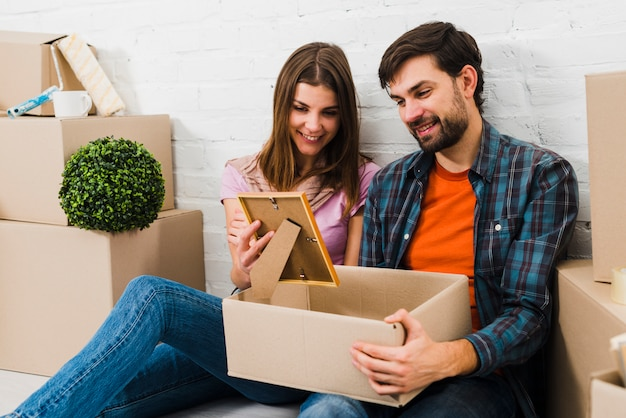 Uśmiechnięty portret młoda para patrzeje ramę brać od kartonu